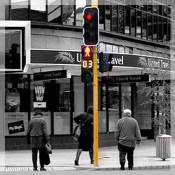 Traffic light on sidewalk with three pedestrians