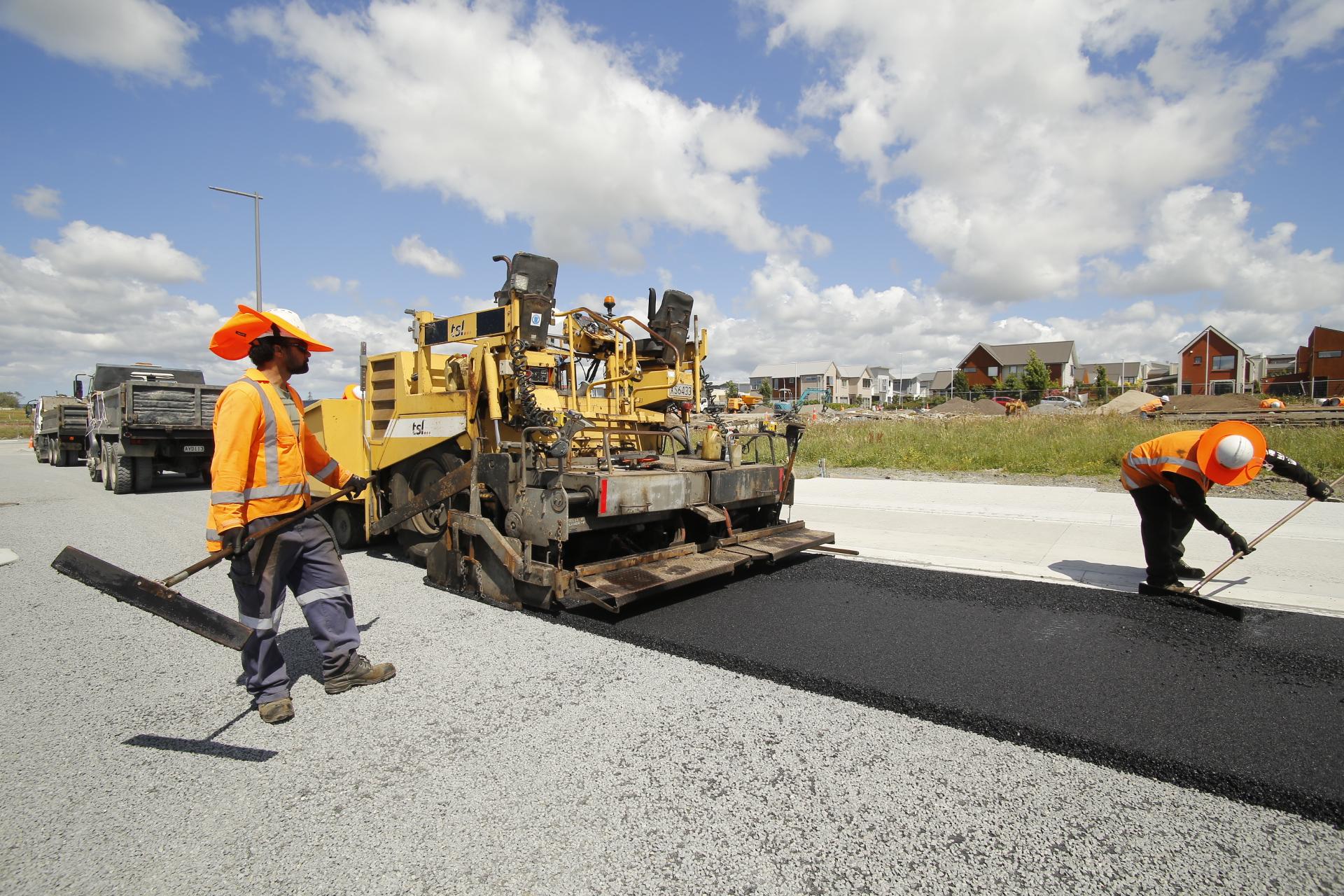 Asphalt paver and workman laying new asphaltic concrete.